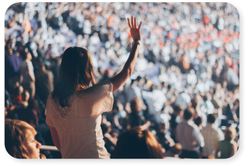 Woman in large crowd holding up her hand