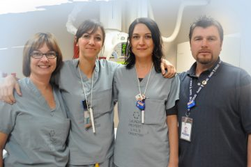 A group of 3 women in grey uniforms and a man in a dark blue polo shirt