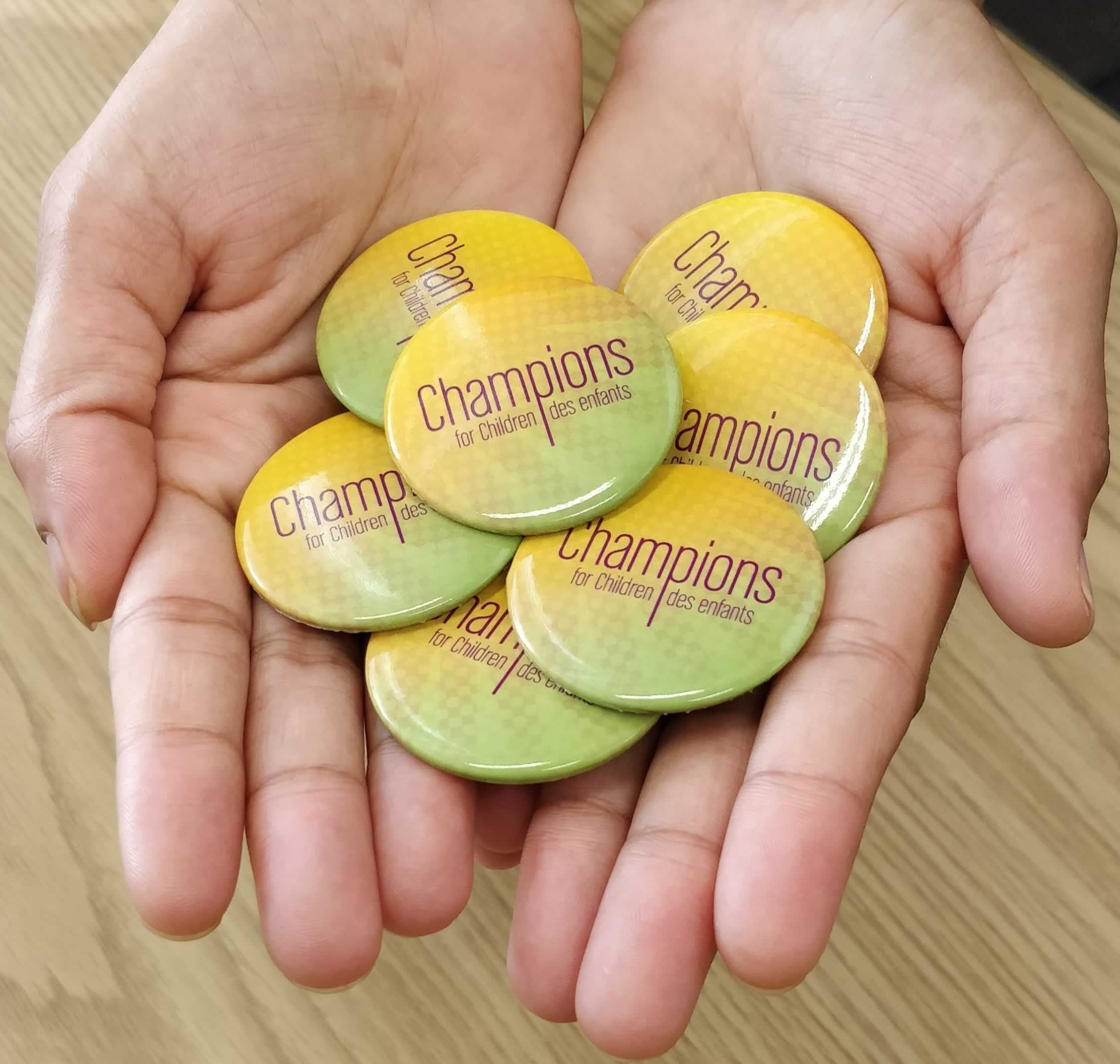 Handful of buttons that say Champions for Children / Champions des enfants