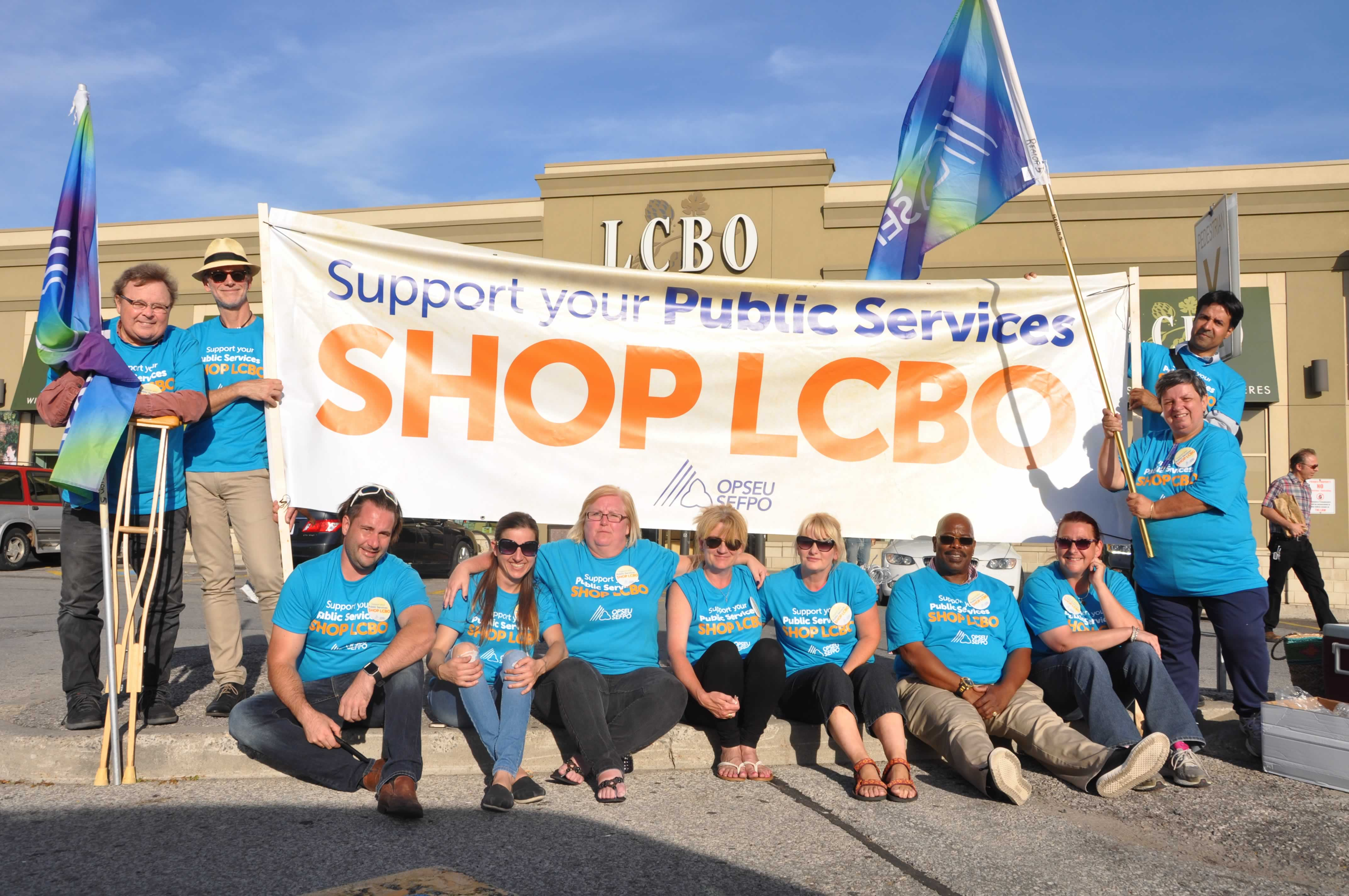 """Group of OPSEU members wearing blue shorts with a large banner that says """"Support your Public Services: Shop LCBO"""""""