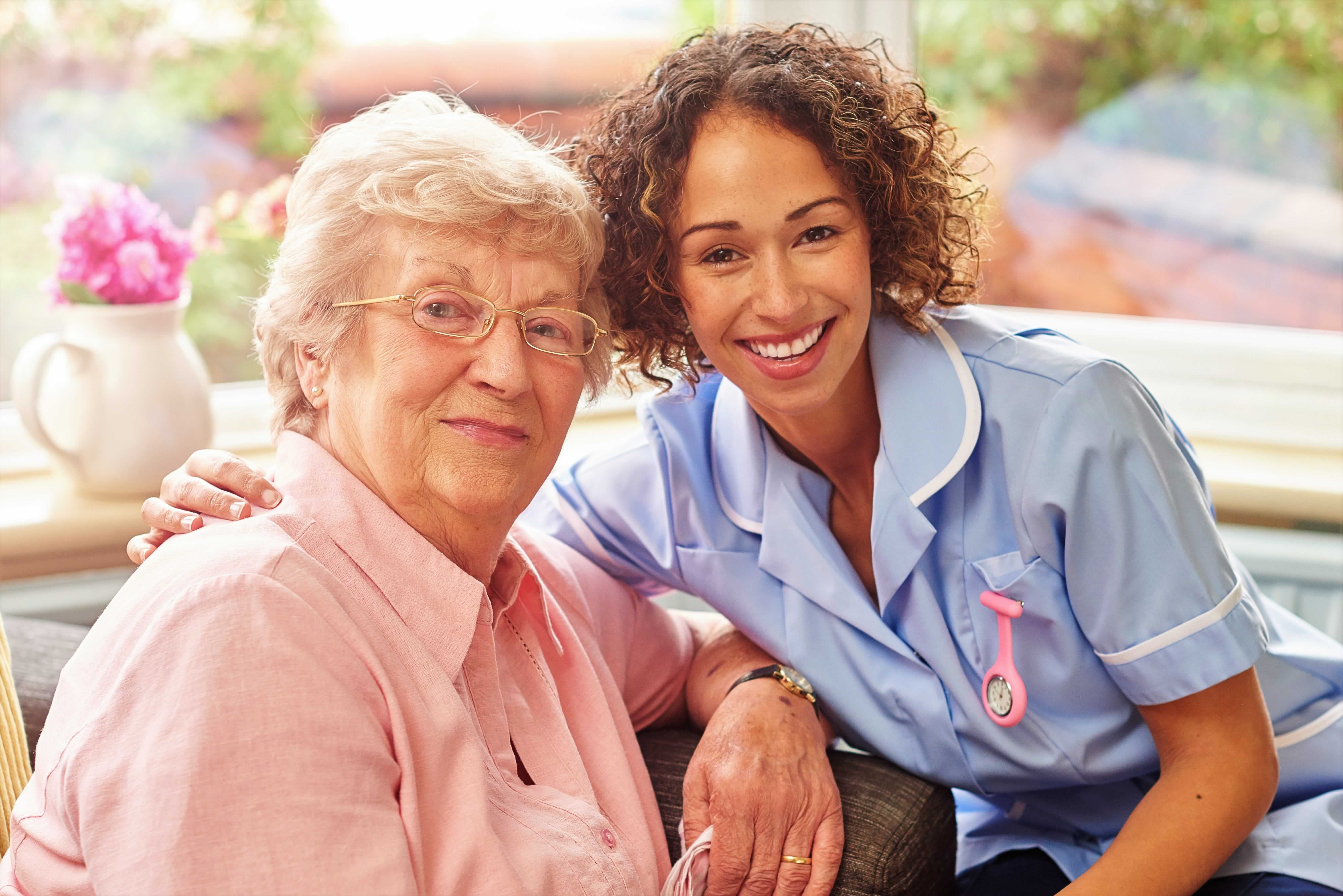 Younger woman in caregiver's attire has her arm round an older woman's shoulder as they smile from a sunlit room