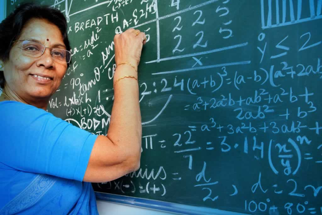 Woman standing at chalkboard writing equations