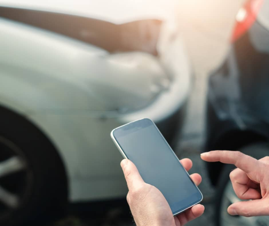 RGI Car Accident. Someone looking at their phone after a car accident